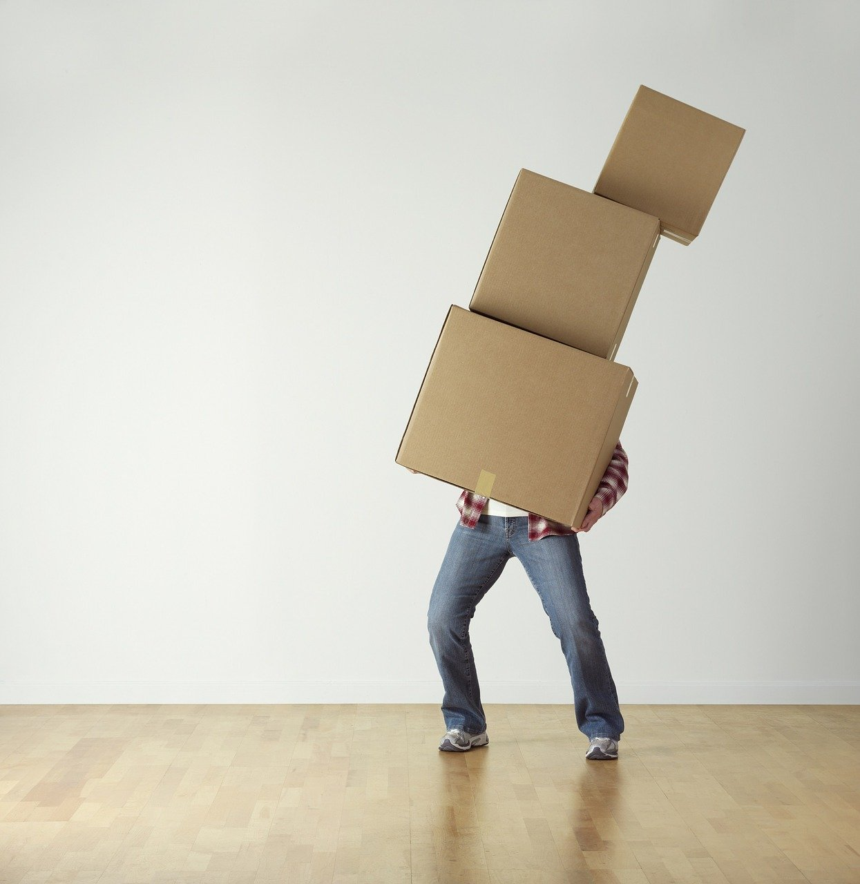a person holding and trying to balance three moving boxes and leaning to one side