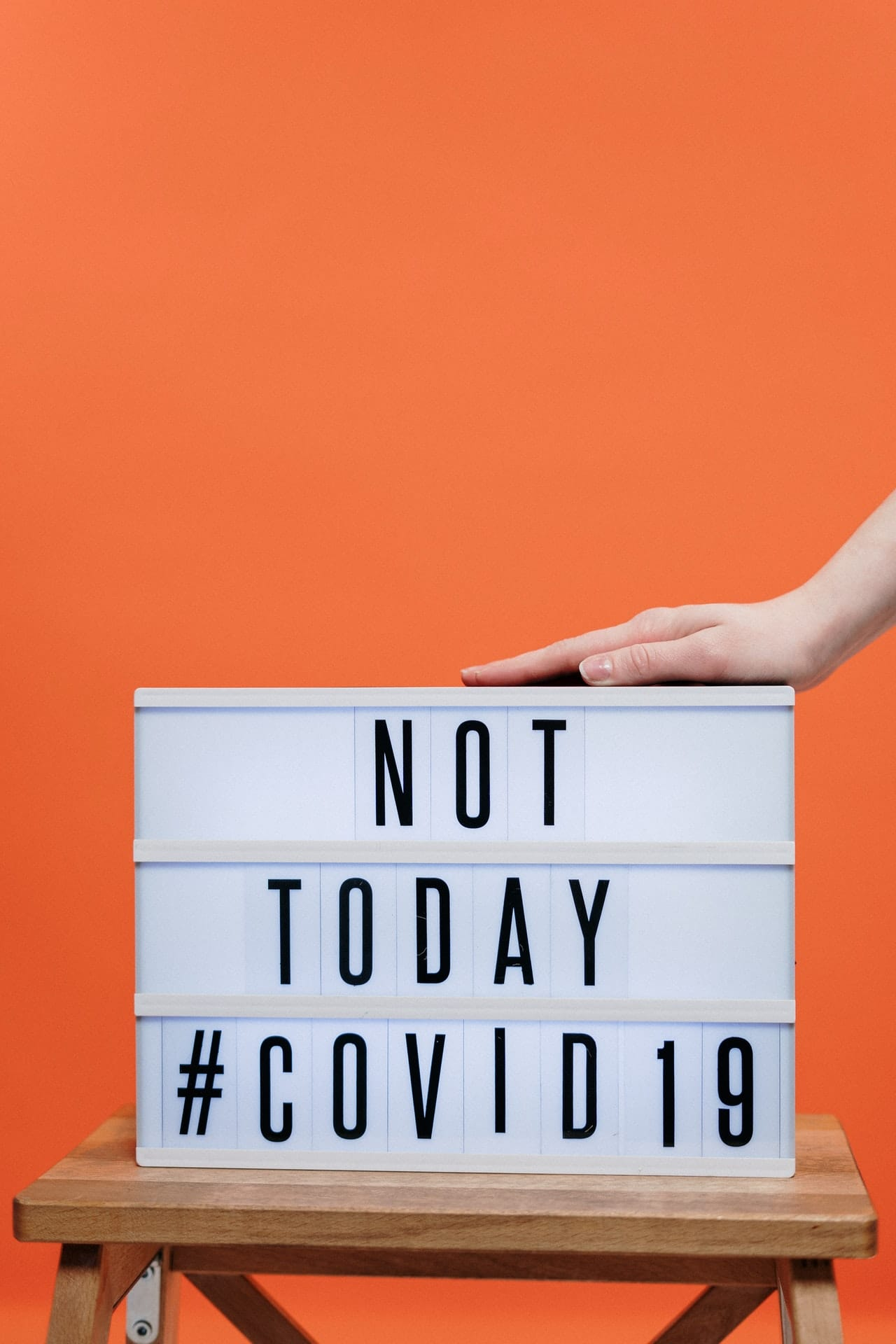 a sign that says not today #covid19 with a hand over it