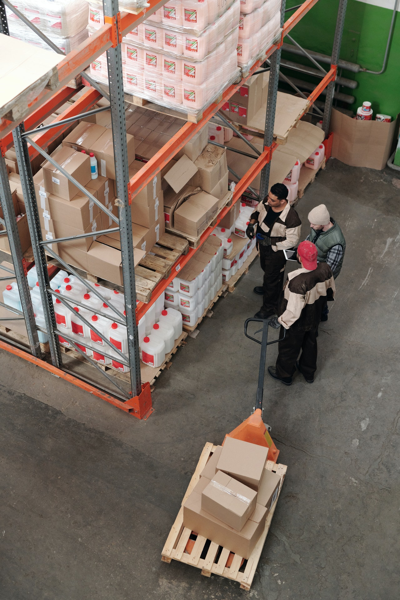 three employees talking inside a warehouse and one holding a dolly